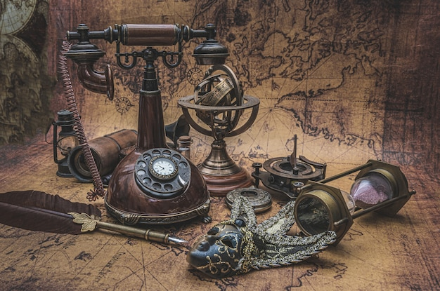 Retro bronze telephone and old collection on old world map Premium Photo