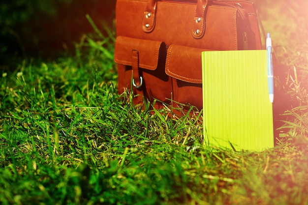 Retro brown  man leather bag and notebook in bright colorful summer grass in the park Free Photo