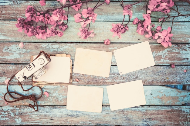 retro camera and empty old instant paper photo album on wood table with flowers border design. Black Bedroom Furniture Sets. Home Design Ideas