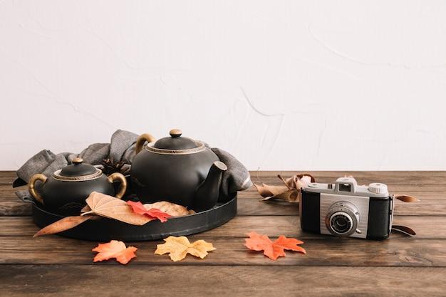 Retro camera near leaves and tea set Free Photo