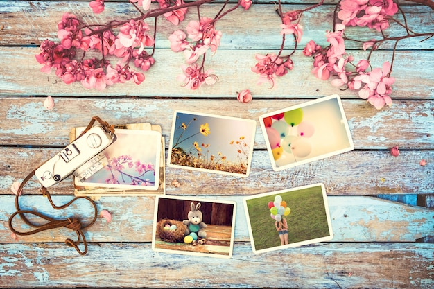 Retro camera and paper photo album on wood table with flowers border design Premium Photo