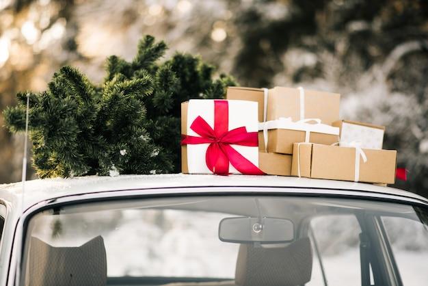 ギフトと雪に覆われた冬の森のクリスマスツリーとレトロな車。休日の装飾、サンタクロースの配達 Premium写真