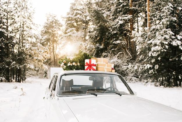 ギフトと冬のクリスマスツリーとレトロな車 Premium写真