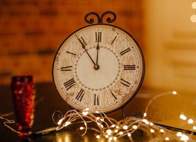 赤いガラスと花輪の近くのテーブルの上に立っている5〜12の手でレトロな時計。スペースをコピーします。 Premium写真