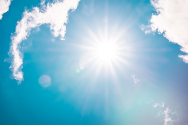 Retro clouds sky with sunbeams and sun flare white fluffy cloudscape nature background Premium Photo
