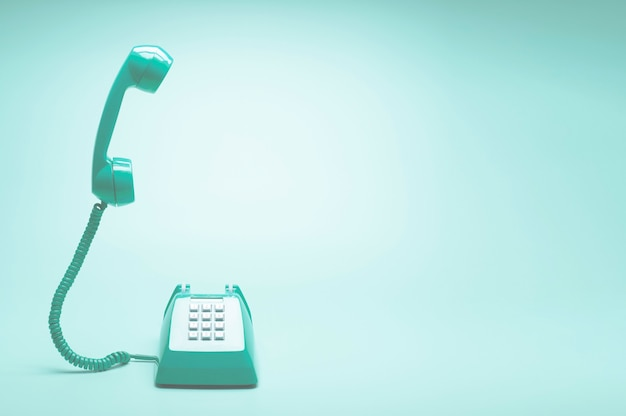 Retro green telephone on teal green background Premium Photo