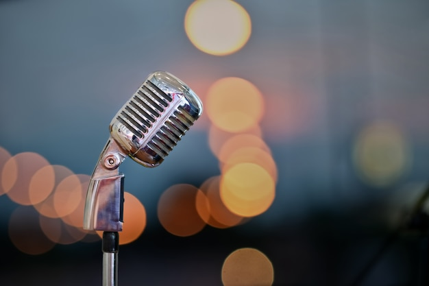 Retro microphone on stage over blurred bokeh background. Premium Photo