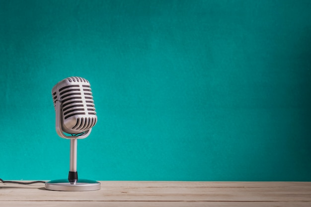 Retro microphone on wooden table with green wall background Premium Photo