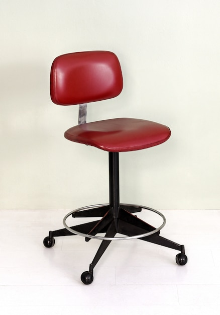 Retro office chair with red seat and wheels Premium Photo