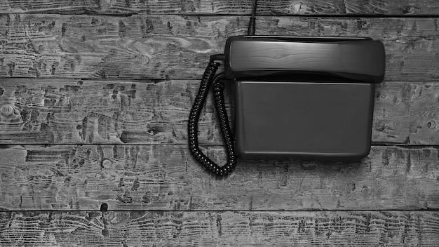 Ретро телефон без возможности набора на черном деревянном столе Premium Фотографии
