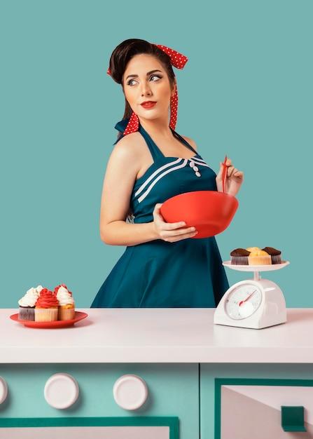 キッチンでポーズをとるレトロなピンナップガール 無料写真