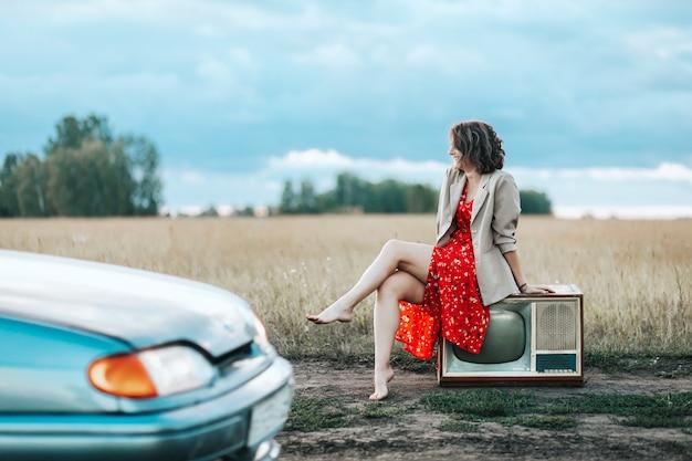 古いテレビに座っている赤いドレスとベージュのジャケットを持つ若い女性のレトロな肖像画 Premium写真