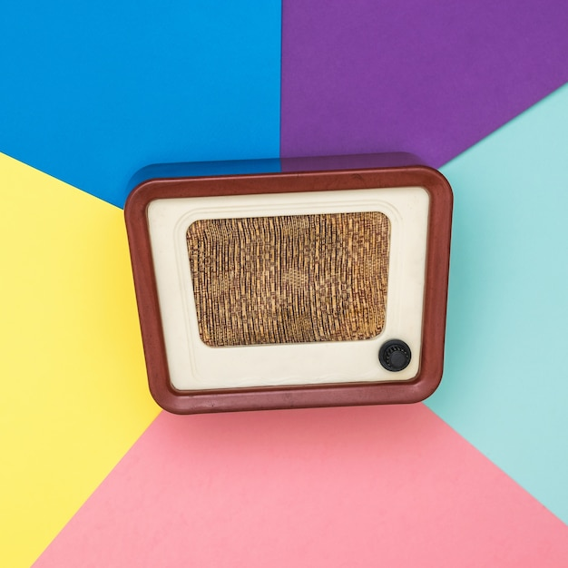 Retro radio on a background of several colors. radio engineering of the past time. retro design. the view from the top. Premium Photo