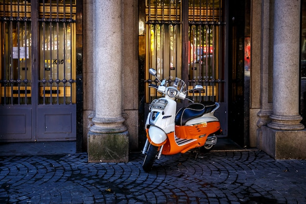 Retro red scooter on the street in a european city. Premium Photo