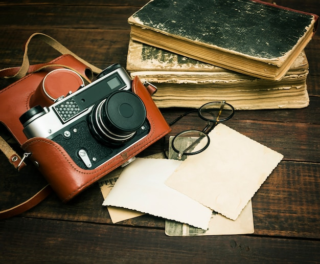 Retro still camera and some old photos on wooden table Premium Photo