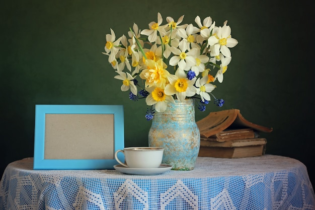 Retro still life with a bouquet of daffodils on a green background. Premium Photo
