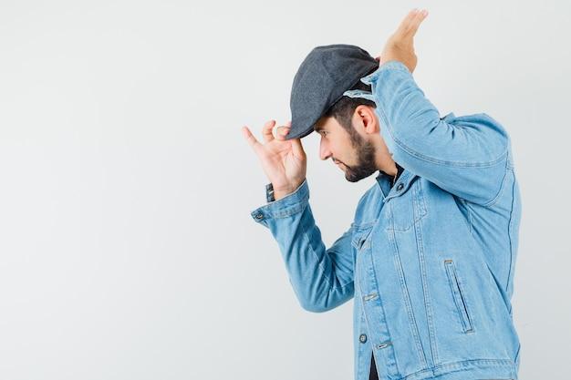 레트로 스타일의 남자 재킷, 모자에 그의 모자를 조정 하 고 초점, 전면보기를 찾고. 텍스트를위한 공간 무료 사진