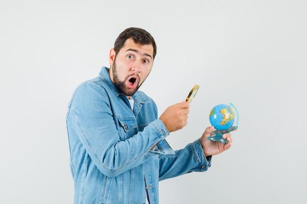 레트로 스타일의 남자 재킷, 돋보기와 미니 지구본을보고 놀란 찾고 티셔츠. 무료 사진