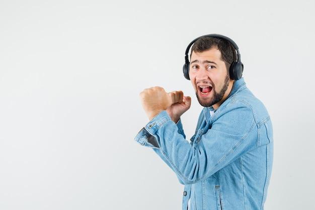 Человек в ретро-стиле слушает музыку с наушниками в куртке, футболке и выглядит удивленным, вид спереди. место для текста Бесплатные Фотографии