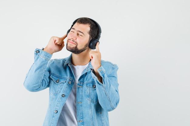 Человек в стиле ретро, слушающий музыку с наушниками в куртке, футболке и расслабленный, вид спереди. Бесплатные Фотографии