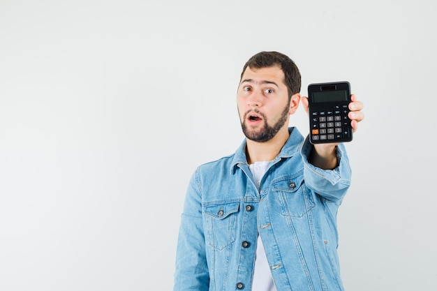 Retro-style man showing calculator in jacket,t-shirt and looking surprised , front view. space for text Free Photo