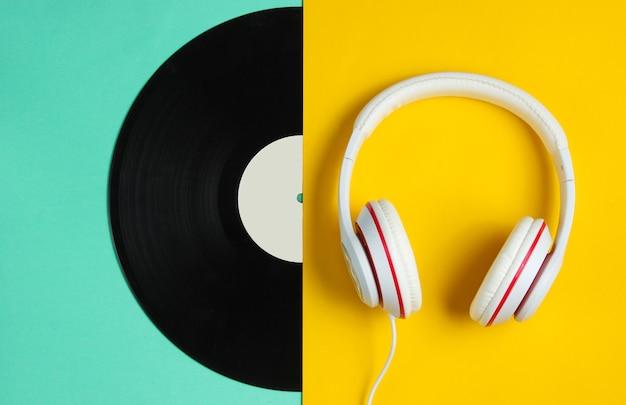 Музыкальная концепция в стиле ретро. классические наушники, половина виниловой пластинки на фоне цветной бумаги. популярная культура. Premium Фотографии