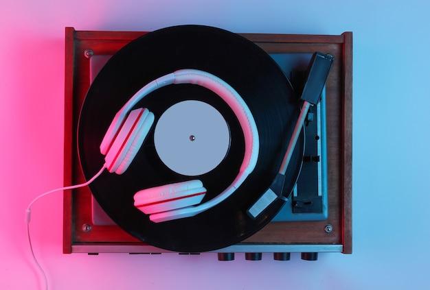 레트로 스타일 음악 개념입니다. 클래식 헤드폰, 그라데이션 핑크-블루 네온 불빛이있는 비닐 레코드 플레이어. 대중 문화. 80 년대. 평면도 프리미엄 사진