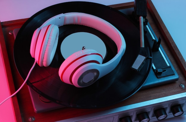 Retro style music concept. classic headphones, vinyl record player with gradient pink-blue neon light. pop culture. 80s. Premium Photo