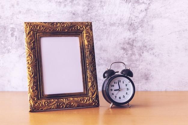 Ретро стиль картинная рамка и будильник на деревянном столе. Premium Фотографии