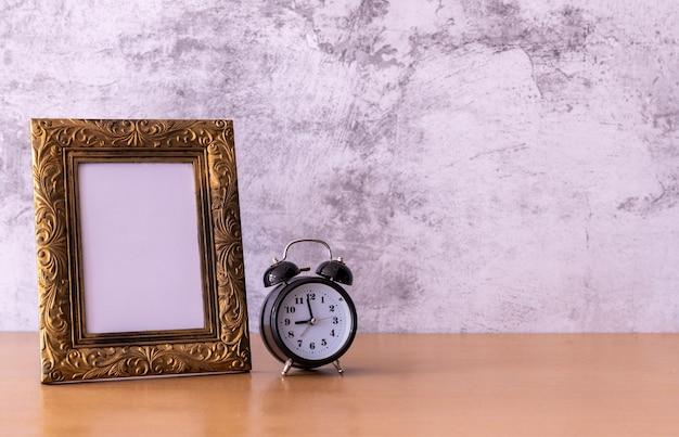 Рамка для фотографий в стиле ретро и будильник на деревянном столе Premium Фотографии
