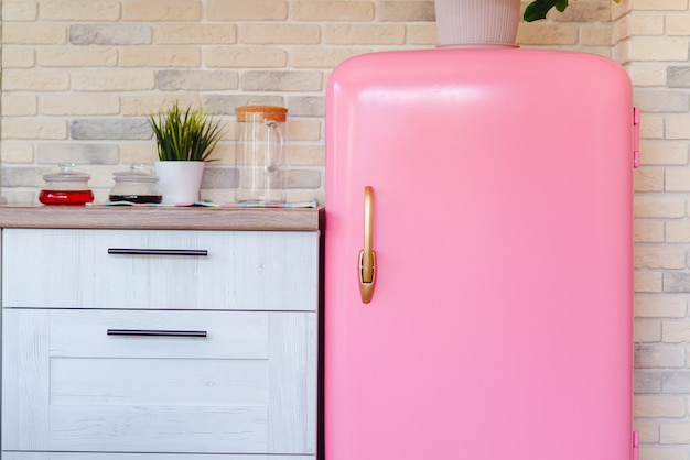 Retro style pink fridge in vintage kitchen Premium Photo