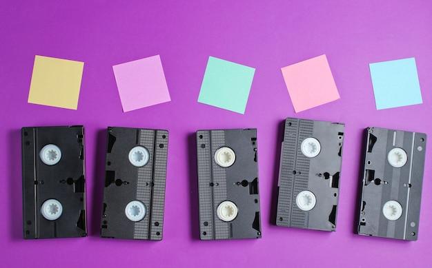 レトロなスタイル、ポップアートのコンセプト。オーディオカセットと紫のメモ用紙。上面図。 Premium写真
