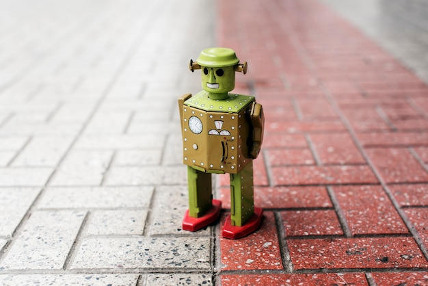 Retro tin robot toy standing on ground with pattern Free Photo