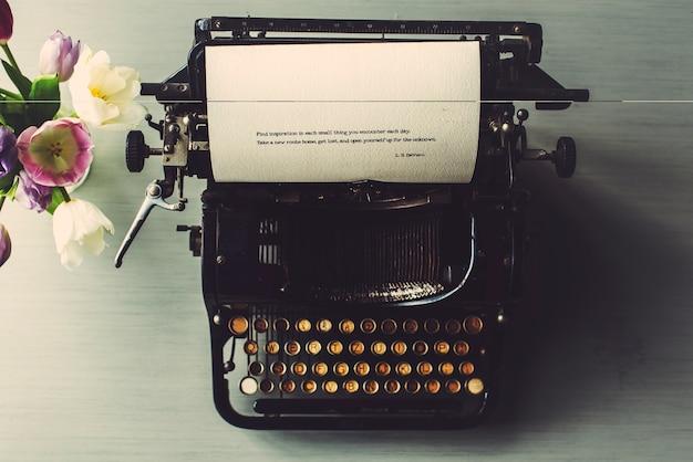 Retro typewriter machine old style by tulips flower Premium Photo