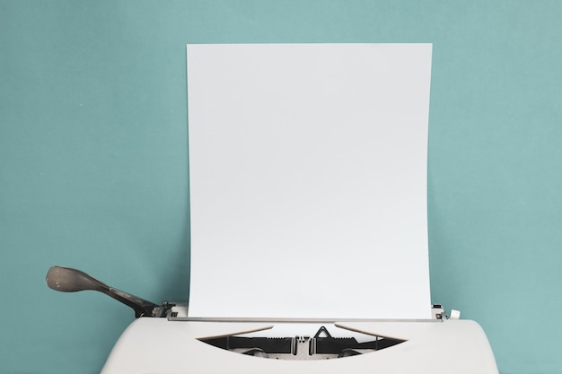 Retro typewriter with blank paper sheet on white wood table front blue wall background with copy space. Premium Photo