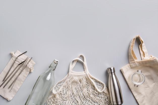 Reusable glass and metal bottle, mesh bag for zero waste lifestyle on grey Premium Photo