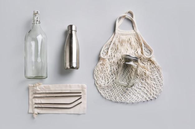 Reusable glass and metal bottle, mesh bag for zero waste lifestyle on grey. Premium Photo