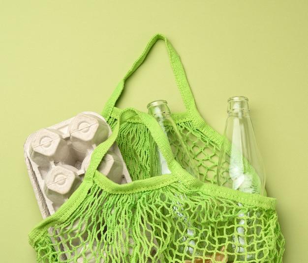 Многоразовая зеленая текстильная сумка для покупок с пустыми бутылками и коробками для яиц на зеленом фоне, без отходов Premium Фотографии