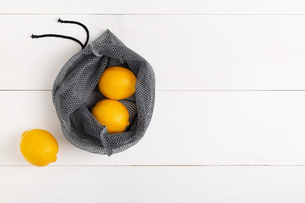 A reusable shopping bag with lemons on white background Premium Photo