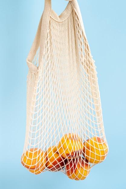 Reusable shopping mesh bag with fruits Free Photo