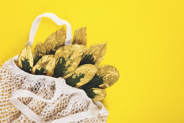 Reusable shopping net bag with green and golden leaves on yellow fall autumn background Premium Photo