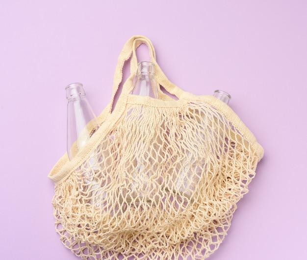 Многоразовая текстильная сумка для покупок с пустыми бутылками на фиолетовом фоне, без отходов Premium Фотографии