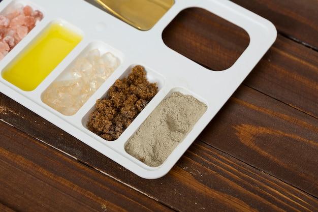 Глина рассола; кофейная гуща; каменная соль и масло на белом подносе против деревянного стола Бесплатные Фотографии