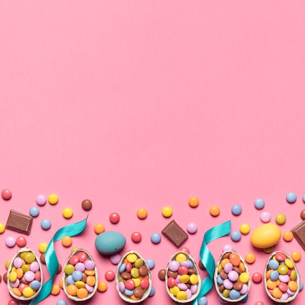 Ribbon; gem candies and easter eggs with space for writing the text on pink backdrop Free Photo