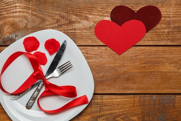 Il nastro nel piatto su legno con un cuore Foto Gratuite