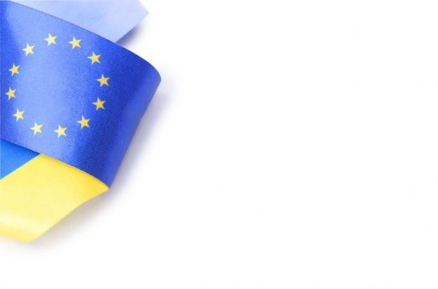 Ribbon with ukrainian and european union flags isolated on white background Premium Photo