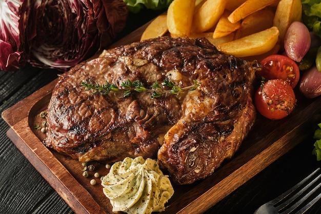 Ribeye steak with potatoes, onions and baked cherry tomatoes Premium Photo