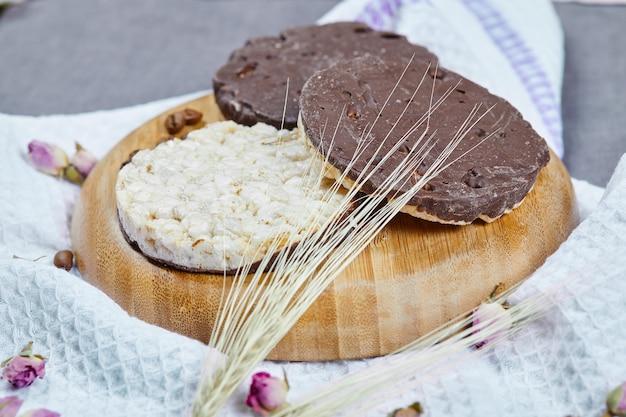 テーブルクロスと木の板の上の米とチョコレートのクラッカー。 無料写真
