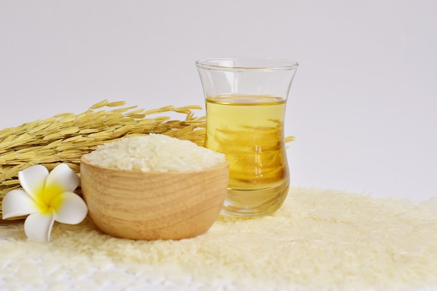 Rice bran oil in a glass with uncooked jasmine rice in wooden bowl & ear of rice on white Premium Photo