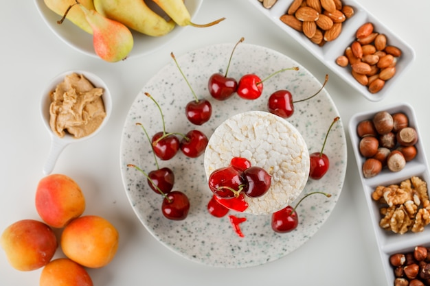 Rice cakes with cherry, nuts, pear, apricot, peanut butter in a plat on white background, top view. Free Photo